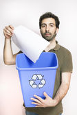 Happy young man throw paper in blue basket — Stock Photo