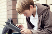 School teen with electronic tablet sitting — Стоковое фото