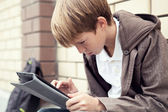 School teen with electronic tablet sitting — Stock Photo