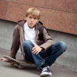 Stock Photo: School teen sits on skateboard near school