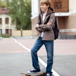 School teen with schoolbag and skateboard — Stock Photo