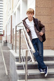Serious boy standing on stairs — Stock Photo