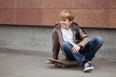 School teen sits on skateboard near school — Stock Photo