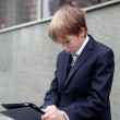 Stock Photo: School boy with electronic tablet sitting,