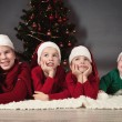 Four children are around Christmas tree. — Stock Photo