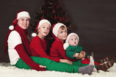 Four children sitting around Christmas tree. — Stock Photo