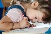 Cute little girl is drawing with pen in preschool — Stock Photo