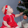 Royalty-Free Stock Photo: Little girl in red dress sitting near Christmas tree