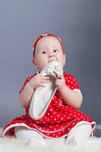 Small girl in red dress holding shoe — Stock Photo