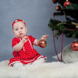 Little girl in red dress sitting near Christmas tree — Stock Photo #15620009