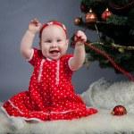 Little girl in red dress sitting near Christmas tree — Stock Photo #15620061