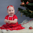 Little girl in red dress sitting near Christmas tree — Stock Photo #15620073