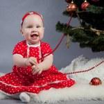 Little girl in red dress sitting near Christmas tree — Stock Photo