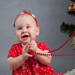 Little girl in red dress sitting near Christmas tree — Stock Photo #15620187