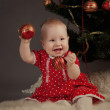 Little girl in red dress sitting near Christmas tree — Stock Photo