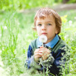 Portrait of boy sitting on grass in park — Stock Photo