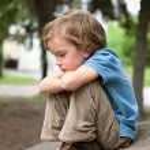 Thoughtful boy sitting on rock — Stock Photo