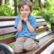 Little boy sits on bench in park — Stock Photo #18752201