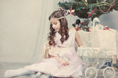 Girl plays with doll around Christmas tree — Stock Photo
