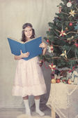Girl reading book around Christmas tree — Stock Photo