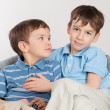 Elder and younger brother sitting on pufe — Stock Photo