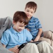 Two brothers playing on tablet — Stock Photo