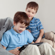 Two brothers playing on tablet - Stock Photo