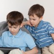 Royalty-Free Stock Photo: Two brothers playing on tablet