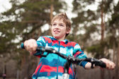Portrait of boy with bicycle in park — Stock Photo