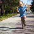 Stock Photo: Boy running along road in park