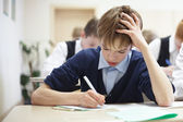School boy struggling to finish test in class. — Stock Photo