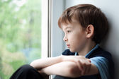 Sad boy sitting on window — Stock Photo