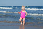 Adorável menina andando ao longo da praia — Foto Stock
