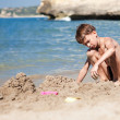 Boy making sand castle on beach — Stockfoto