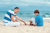 Father and son sitting on sea — Stock Photo