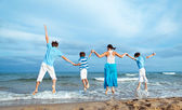 Mother and three sons are jumping on beach — Stock Photo