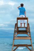 ライフガードの椅子に座っている少年 — ストック写真