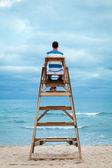 Uomo seduto sulla sedia del bagnino — Foto Stock