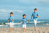 Three brothers are running on beach — Stock Photo