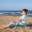 Thoughtful boy sitting on chair at beach — Stock Photo