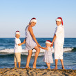 Children in santa claus hat are standing on beach — Stock Photo
