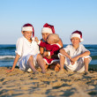 Stock Photo: Children in santa claus hat are sitting on beach