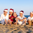 Children in santa claus hat are sitting on beach — Stock Photo