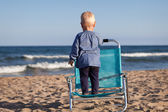 Happy little girl standing on chair at beach — Stock Photo