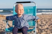 Happy little girl sitting on chair at beach — Stock Photo