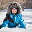 Boy in winterwear laughing while playing in snowdrift outside — Stock Photo