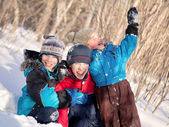 Children in winterwear laughing while playing in snowdrift — Stock Photo