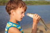 Boy holding fish and smiling — Stock Photo