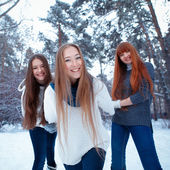 Portrait of three beautiful girls in winter park — Стоковое фото