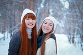 Portrait of two beautiful girls in winter park — Stock Photo
